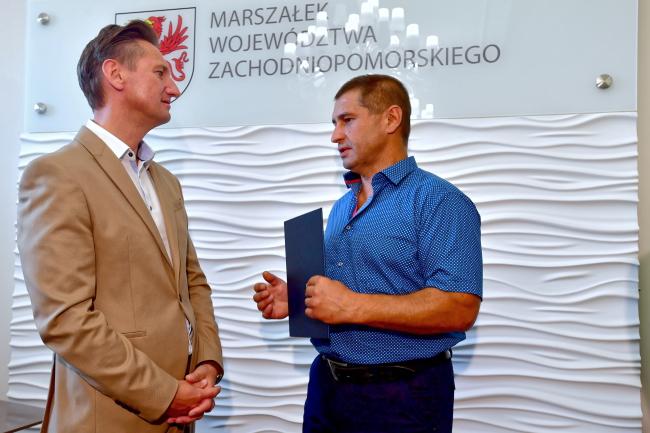 Водитель из Украины Андрий (справа) получает благодарность от главы Западно-Поморского воеводства Ольгерда Геблевича (слева)