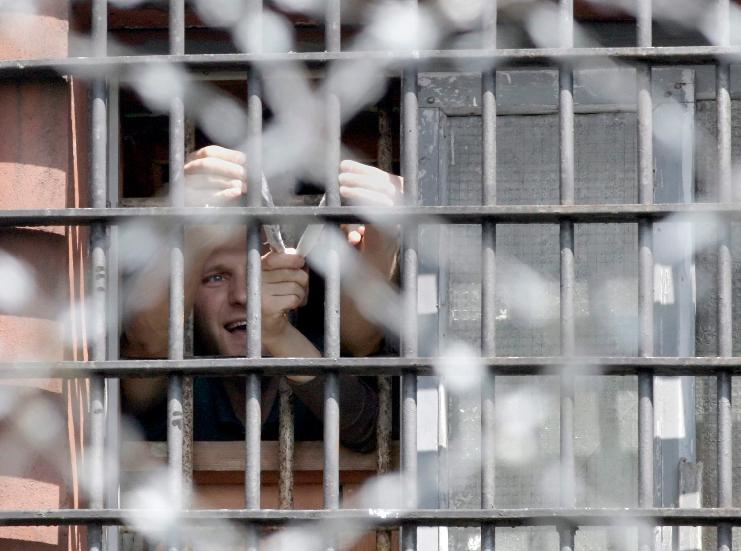 An imprisoned Belarusian protestor holds a slingshot in a prison cell to catapult a message for his relatives and friends who wait outside the prison walls to bring food and clothes in Minsk, Belarus, 07.07.2011.Photo: PAP/EPA/Tatyana Zenkovich