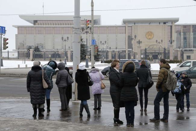 People stand opposite the Palace of Independence where the 'Normandy Four' meeting will take place in Minsk. Germany and France are spearheading a new peace drive, and their talks with Ukraine and Russia are planned for 11 February in the Belarusian capital. Photo: PAP/EPA/MAXIM SHIPENKOV