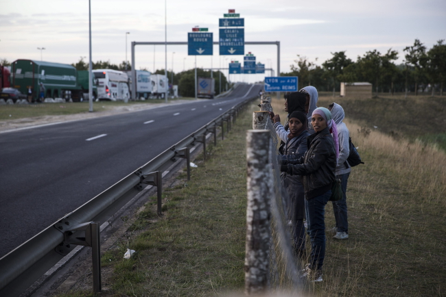 Migrants wait before they jump over a fence next to a road and try to cross the fences to the rail tracks on the outskirts of Calais, France, 04 August 2015. EPA/ETIENNE LAURENT