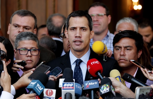 Juan Guaido (centre), the head of the Venezuelan National Assembly, speaks to the press in Caracas on Tuesday. Photo: EPA/LEONARDO MUNOZ