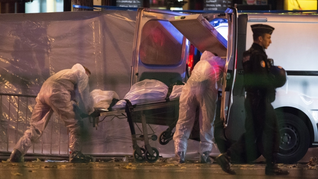 Medical staff carry the body of a victim in front of the Bataclan theatre in Paris, France, 14 November 2015. At least 120 people have been killed in a series of attacks in Paris on 13 November, according to French officials. Photo: EPA/MARIUS BECKER