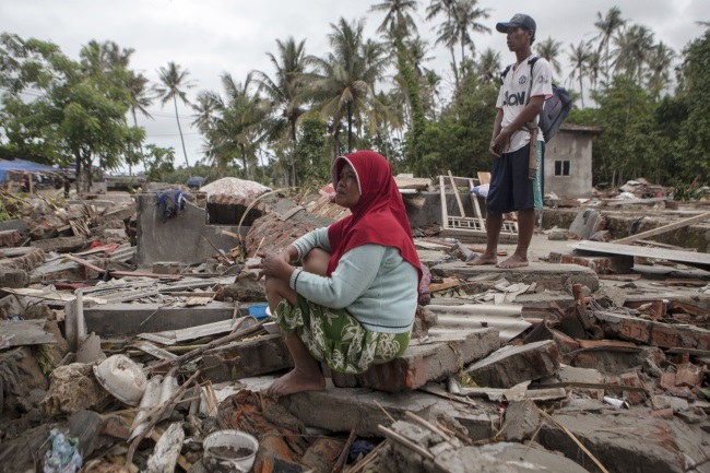 An Indonesian tsunami victim sits on the ruins of her house on Tuesday. Photo: EPA/ZULKIFLI