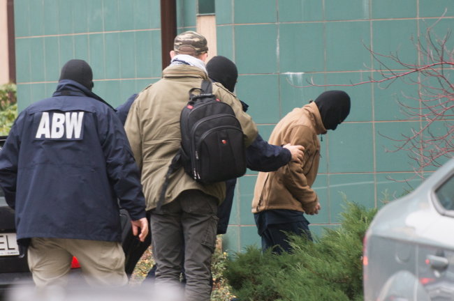 Officers from Poland's Internal Security Agency (ABW) bring a suspect accused of fighting for jihadists in Syria to the Prosecutor's Office in Łódż, 16 November. Photo: PAP/Grzegorz Michałowski