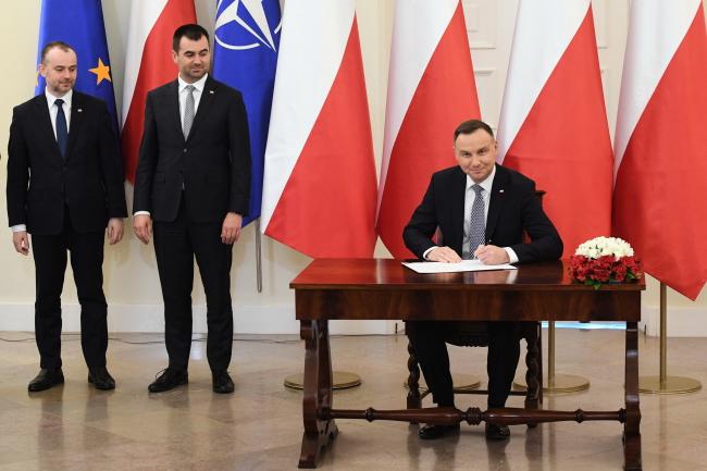 Президент Польши Анджей Дуда (справа) подписывает закон о 13-й пенсии
