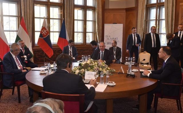 Президент Чехии Милош Земан (слева), президент Словакии Андрей Киска (в центре), президент Польши Анджей Дуда (справа) и президент Венгрии Янош Адер (спиной к камере) сидят за столом переговоров во время саммита президентов стран Вышеградской группы в Штрбске-Плесо