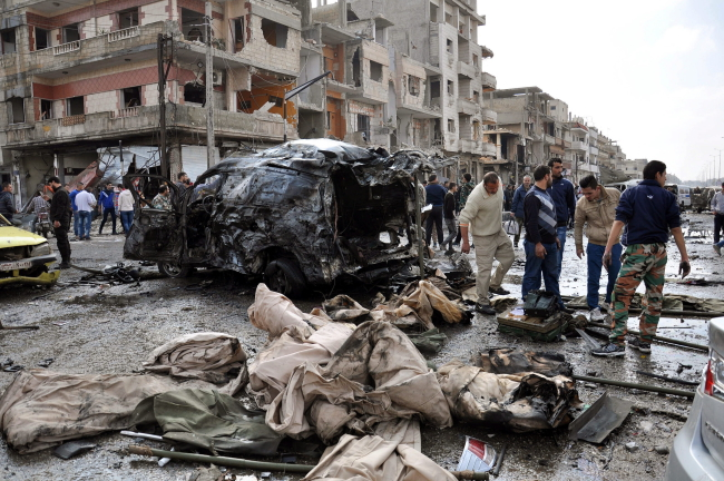 Syrian policemen and citizens inspect the site of a twin bomb attack in the city of Homs, Syria, 21 February 2015.EPA/STR