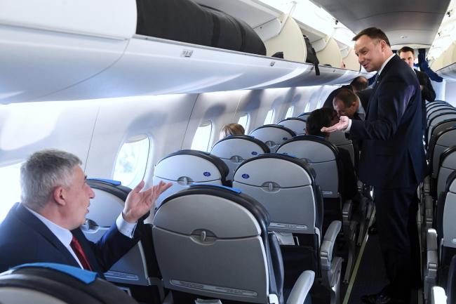 Анджэй Дуда (стаіць у праходзе) на борце самалёта на шляху ў Швэйцарыю