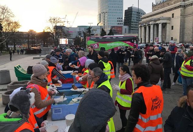 Волонтеры Smile Warsaw кормят бездомных на площади Дефиляд в Варшаве