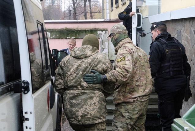 Сотрудники Федеральной службы безопасности России (справа) сопровождают задержанного моряка ВМС Украины (слева) на судебное заседание в Симферополе