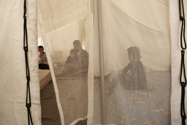 An Afghan family find shelter inside a tent at a transit camp in the western Athens' suburb of Schisto, Greece 18 May 2016. Photo: EPA/YANNIS KOLESIDIS