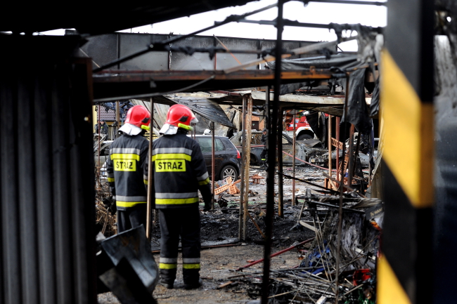 Firemen survey at the burnt out market in Osinów Dolny, western Poland. Photo: PAP/Marcin Bielecki