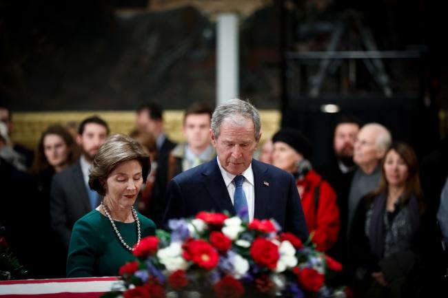 Джордж Буш разам з сужэнкай Лорай каля труны бацькі